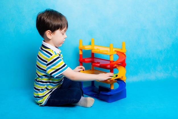 青い背景の駐車場のおもちゃで車で遊ぶ少年