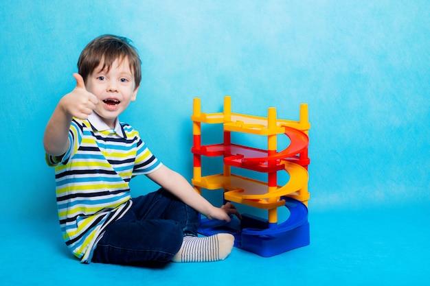 駐車場で車で遊ぶ少年。子供のおもちゃ。少年は青い表面に駐車するゲームをします車のための明るい駐車場。幸せな子供時代