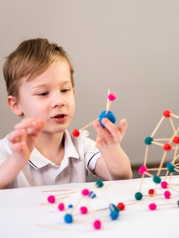 Boy playing with colorful atoms game indoors