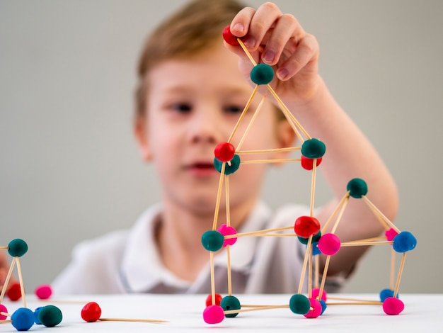 Мальчик играет с красочными атомами игры на столе