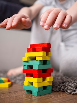 Boy playing with colorful wooden tower game