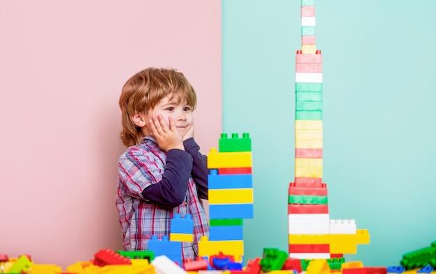Мальчик играет со строительными блоками в детском саду. ребенок играет с красочными игрушечными блоками. развивающие игрушки для детей младшего возраста. маленький мальчик играет с большим количеством красочных пластиковых блоков конструктора.
