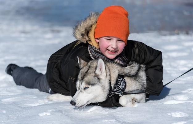 Мальчик играет с собакой зимой в парке