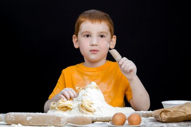 台所で小麦粉で遊ぶ少年