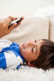 Boy playing with his cellphone while lying on the carpet