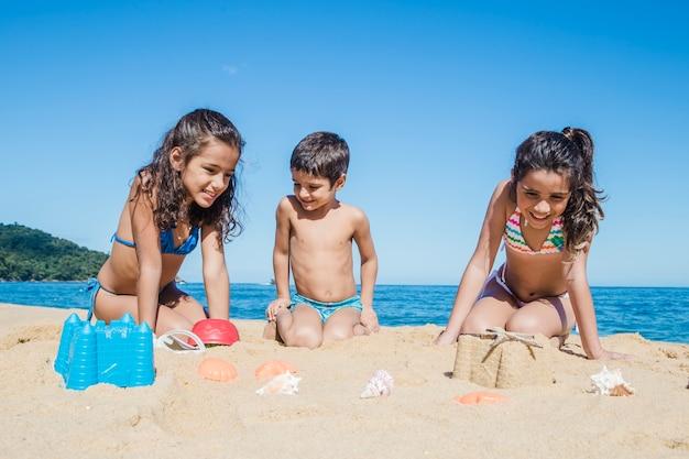 Ragazzo che gioca con le sue sorelle sulla sabbia
