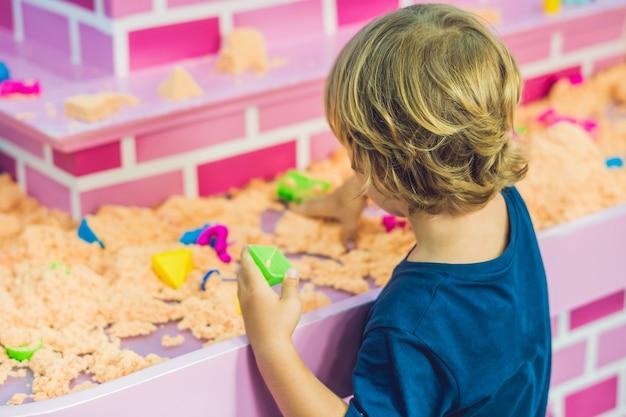 Мальчик играет с кинетическим песком