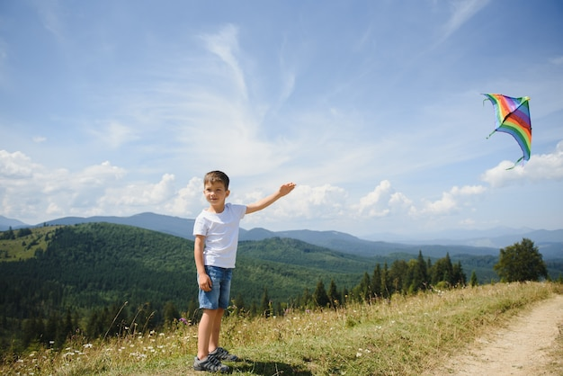 Boy playing with a kite in the mountains