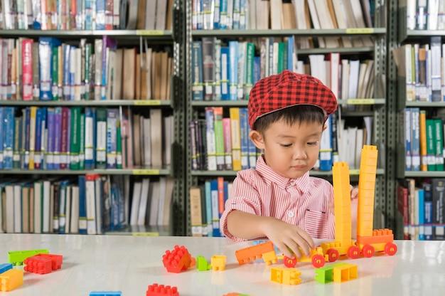 図書室の学校でプラスチック製のブロックで遊んでいる少年