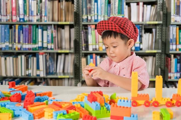 도서관 방 학교에서 플라스틱 블록을 가지고 노는 소년