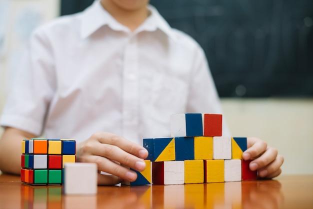Ragazzo che gioca con i puzzle alla scrivania