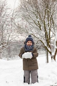 겨울 시즌에 눈을 가지고 노는 소년. 강설 후 흰 눈으로 뒤덮인 공원 내 위치. 사진 근접 촬영.