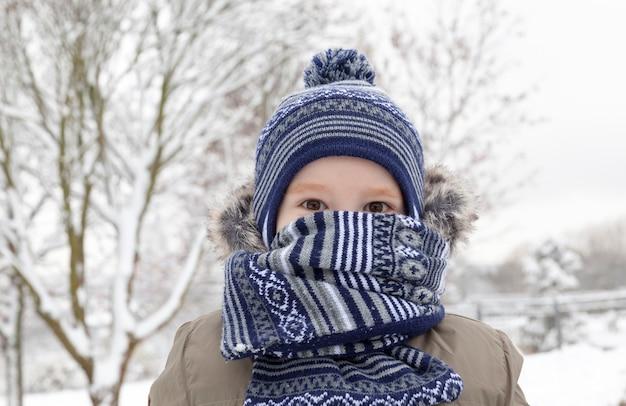冬の雪で遊ぶ少年。子供は霜のためにスカーフに隠れました。降雪後の白い雪に覆われた公園内の場所。写真のクローズアップ。