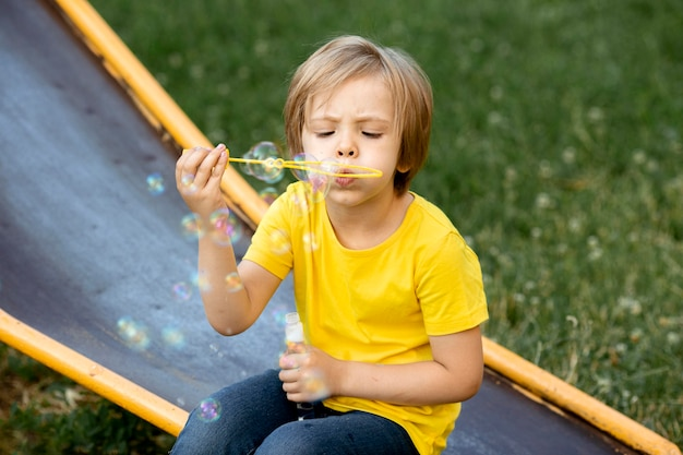 Мальчик играет с мыльными пузырями