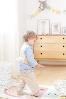 Boy playing with toys in the room. eco-friendly children's room decor in the scandinavian. portrait of a boy playing in kindergarten. children's room and interior design. the boy is at home. little boy