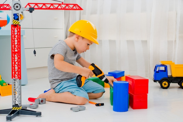 Boy plays in the builder in the room