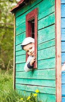 少年は屋外の小さなおもちゃの木造住宅で遊ぶ