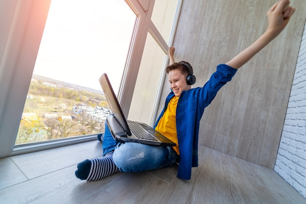 소년은 발코니에서 노트북을 가지고 놀고 있습니다. 아이가 비디오 게임에서 방금 이겼습니다. 아이들은 집에 있습니다. 학교가 없습니다.