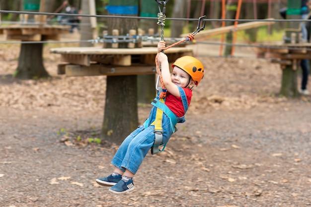 Мальчик играет на детской площадке в канатном городке
