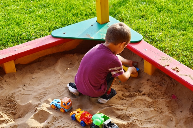 Boy plays in a sandbox on playground with toy figures