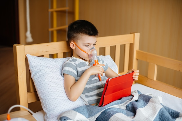 Boy plays on a tablet during a lung inhalation procedure. medicine and care