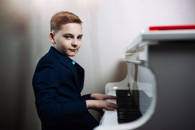 소년은 피아노를 연주합니다. 세련된 어린이가 악기를 연주하는 법을 배웁니다.