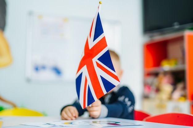 Boy plays with british flag. child holds the flag of great britain. english flag in girl's hands.