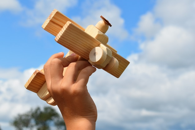 Boy plays with handmade wooden plane