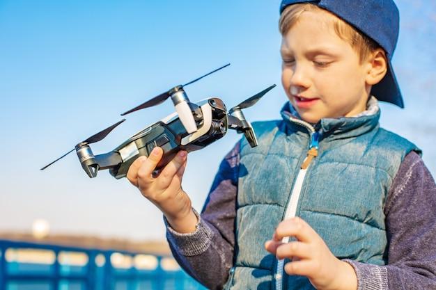 Мальчик играет со своим дроном в парке