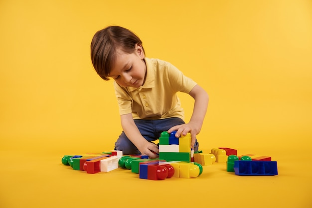 Boy plays with plastic toy bricks. children leisure concept.