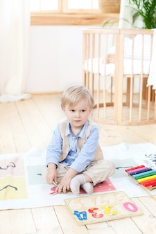 The boy plays with wooden toys at home. educational wooden toys for the child. portrait of a boy sitting on the floor in the children's room in the scandinavian style. eco toys, children's room decor