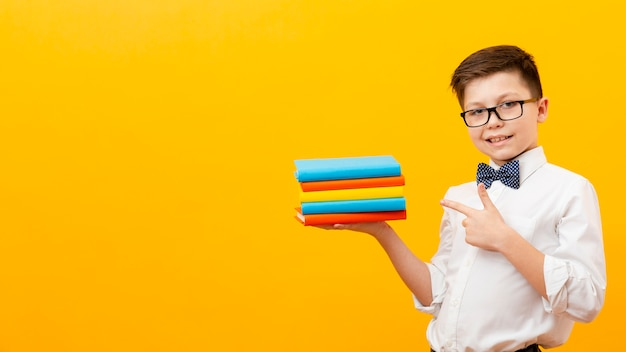 Boy pointing at stack of books