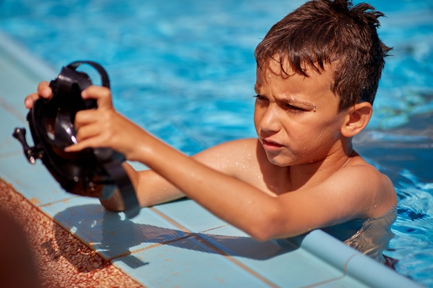 Boy in the pool is wearing a mask