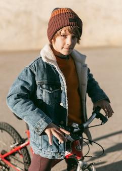 彼の自転車で街の屋外でポーズをとる少年
