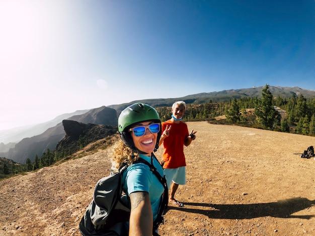 山の風景で自分撮りをしている母親と一緒にポーズをとる少年。明るい晴れた日に山でポーズをとる彼女の10代の息子と一緒にselfieを取るヘルメットとサングラスで幸せな女性旅行者