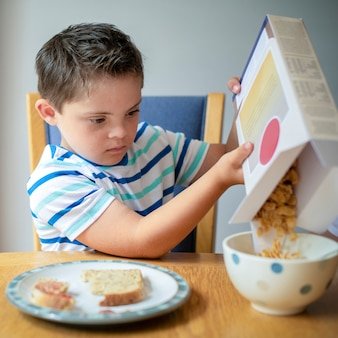 Boy pouring cornflakes into a bowl
