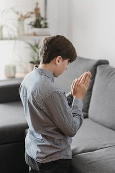 Ragazzo che prega nel soggiorno