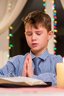 Boy praying at the table. kid prays at nighttime. christmas prayer at city church. youthful parishioner on christmas.