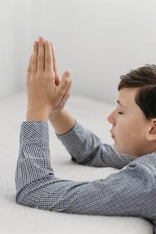 Ragazzo che prega con le sue mani sul cattivo