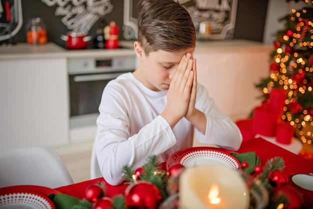 Boy prays at festive table before christmas dinner