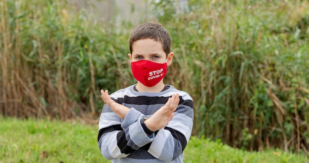 소년은 마스크를 쓰고 질병 바이러스의 확산을 보호합니다. 보호 마스크에 백인 소년의 초상화입니다. 코로나 바이러스 감염증 -19 : 코로나 19. 대유행 중 코로나 바이러스 예방. 보건 의료. 보호 개념
