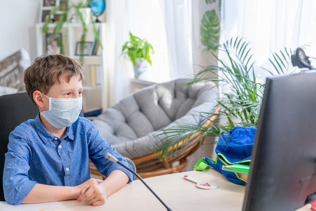 Boy in protective mask, sitting at computer, watching training video