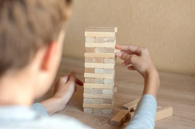 少年は木の塔からブロックを引き出します