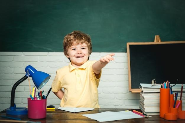 Мальчик ученик начальной школы во дворе школы. веселый улыбающийся маленький мальчик ученик с удовольствием против доски. концепция образования и чтения. день учителя.
