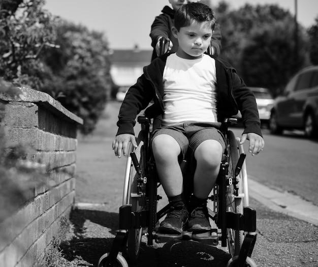 Мальчик толкает своего брата в инвалидной коляске