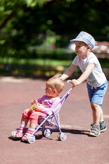 Boy pushing sister in a stroller