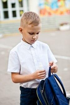 소년은 학교 가방에 손을 소독하기 위해 소독제나 소독제 스프레이를 넣었습니다. 코로나바이러스 검역, 전염병 예방 개념.