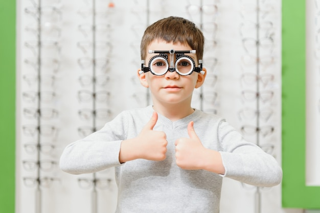 Boy put trial frame at clinic medical optician concept.