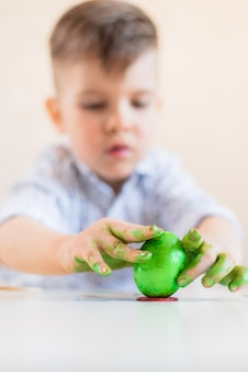 A boy puts a green easter egg on a stand with his hands stained with paint on a white table.