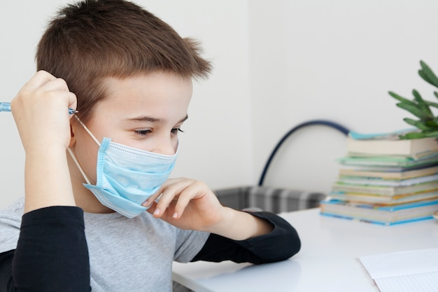 A boy puts a medical mask on his face. quarantine home education during coronavirus